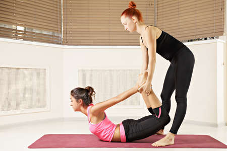 Yoga instructor helping brunette in back bend pose Stock Photo