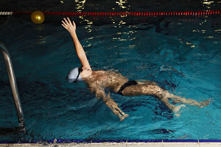 Kid in goggles swimming backstroke in swimming pool photo