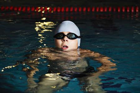 Kid in goggles enjoying swimming pool photo