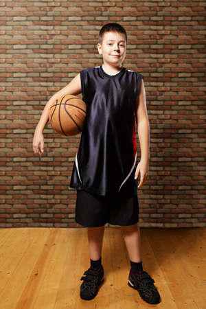 contented: Contented kid with basketball standing against wall