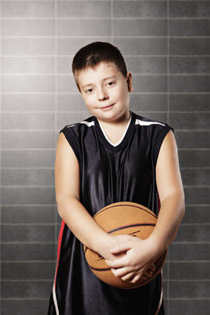 Contented kid holding basketball against gray wall photo
