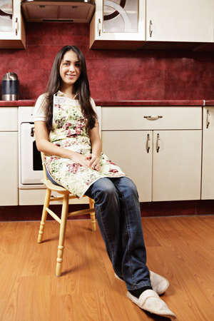 pleasant emotions: Brunette woman in kitchen sitting on chair Stock Photo