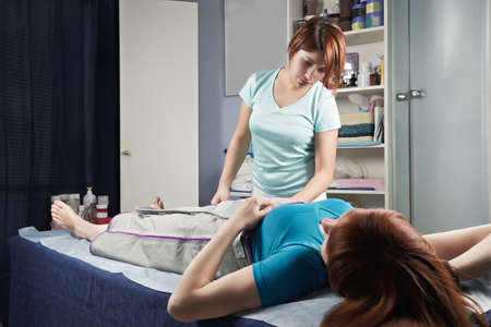 Masseuse looking at redhead woman at air compression massage procedure purposed for lymphatic drainage improvement