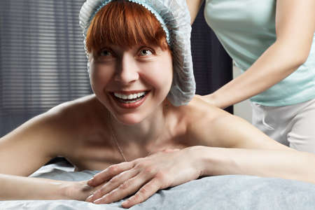 pleasant emotions: Funny middle-aged caucasian redhead woman having a massage