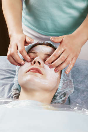 making face: Masseuse making face massage to middle-aged caucasian woman