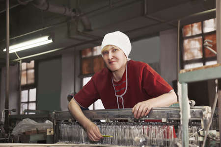 smock: Positive blonde caucasian woman in red smock standing at the factory workshop with yellow comb Stock Photo