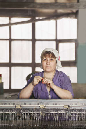 smock: Caucasian woman in purple smock standing at the machine with thread in hand