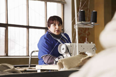 smock: Seamstress in blue smock against window at the factory Stock Photo
