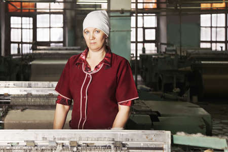 smock: Caucasian woman in red smock standing at the factory workshop