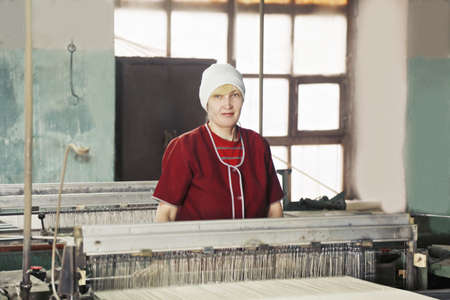 smock: Blonde caucasian woman in red smock standing at the factory workshop Stock Photo