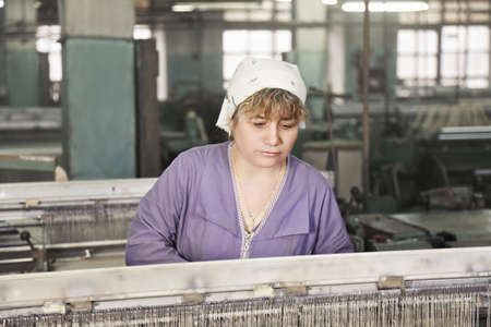 smock: Caucasian woman in purple smock working on the machine at factory Stock Photo