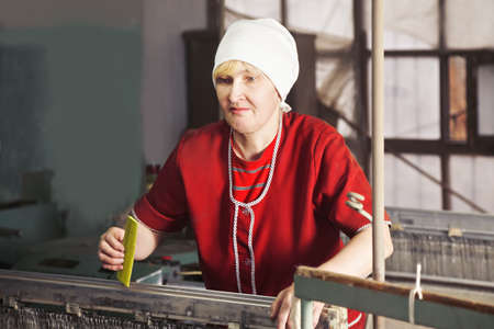 smock: Blonde caucasian woman in red smock standing at the factory workshop with yellow comb