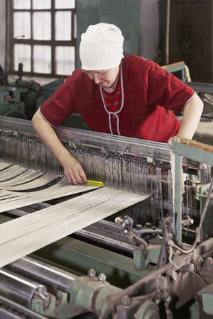 smock: Caucasian woman in red smock straightens threads with a yellow comb at factory Stock Photo