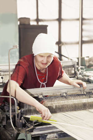 smock: Positive caucasian woman in red smock straightens threads with a yellow comb at factory