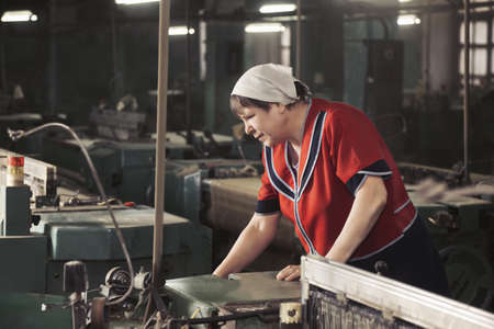 smock: Senior caucasian woman in red smock working on the machine at factory sideview Stock Photo