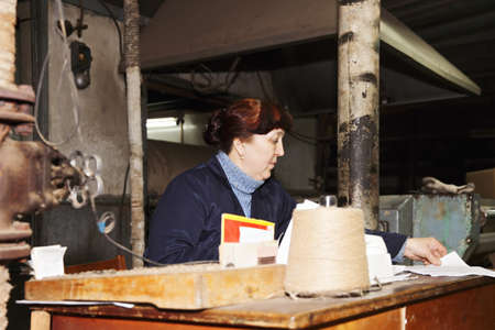 smock: Caucasian forewoman in a blue smock at her workplace in dark workshop Stock Photo
