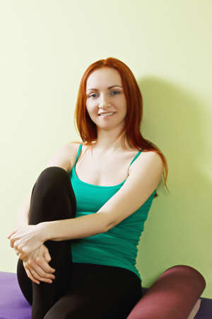 pleasant emotions: Positive caucasian redhead woman sitting on a bench at gym closeup photo
