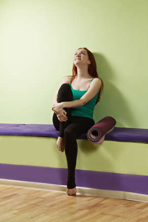 pleasant emotions: Smiling caucasian redhead woman sitting on a bench at gym with rolled mat aside
