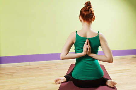 hatha: Palms of redhead caucasian woman folded behind back exercising hatha yoga in a gym rear view