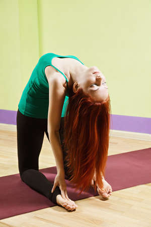 inclined: Caucasian woman with long red hair inclined backwards at yoga class
