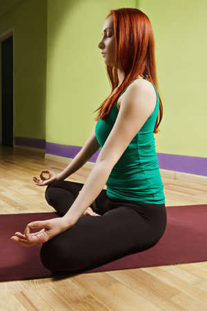 sideview: Caucasian redhead woman in green shirt at lotus pose meditation sideview