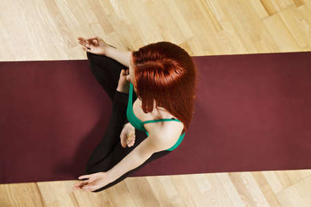 vertical wellness: Redhead caucasian woman meditating in lotus position high angle view