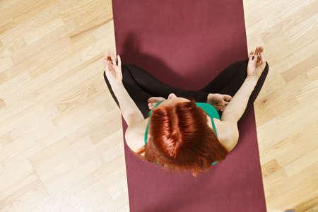 yoga mat: Above view at lotus yoga pose taken by caucasian redhead woman wearing green shirt Stock Photo