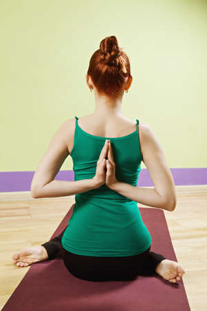 hatha: Palms folded behind back of redhead caucasian woman wearing green shirt exercising hatha yoga in a gym Stock Photo