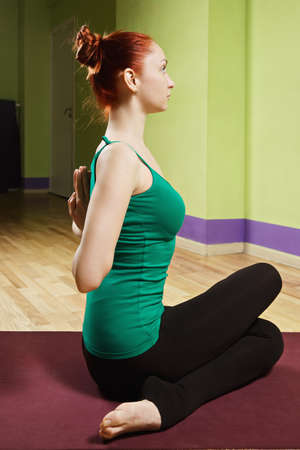 sideview: Palms of redhead caucasian woman folded behind back exercising hatha yoga in a gym sideview