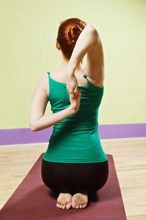 vertical wellness: Hand clutched behind back yoga pose Stock Photo