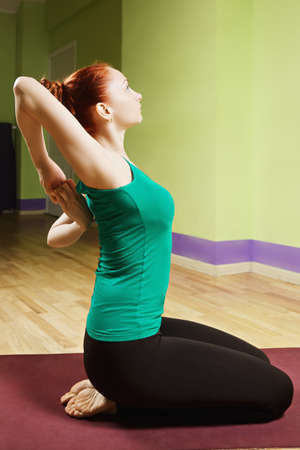 sideview: Hand clutched behind back yoga pose sideview