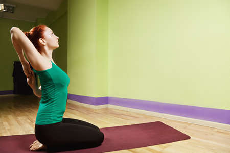 hand position: Hand clutched behind back yoga position profile view Stock Photo