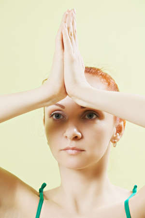 vertical wellness: Serious caucasian woman with palm folded at the forehead