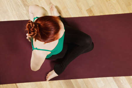 hatha: Palms of redhead caucasian woman folded behind back exercising hatha yoga in a gym above view