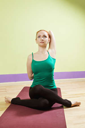 vertical wellness: Redhead caucasian woman in green shirt exercising clutch behing back yoga position at gym