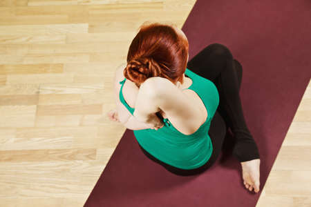 high angle view: Hand clutched behind back yoga pose high angle view Stock Photo