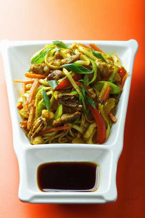 stir fried: Stir fried noodles with meat and vegetables over orange tabletop Stock Photo