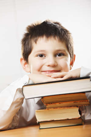 pleasant emotions: Smiling caucasian boy in classroom leaning on stack of books in classroom