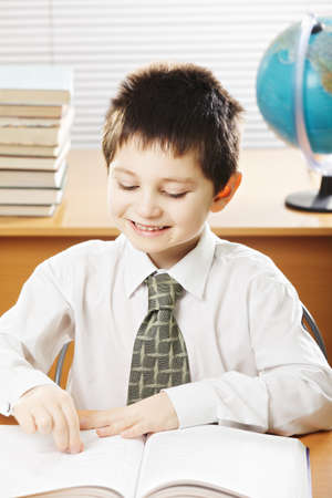 pleasant emotions: Smiling caucasian boy reading book at the desk in classroom
