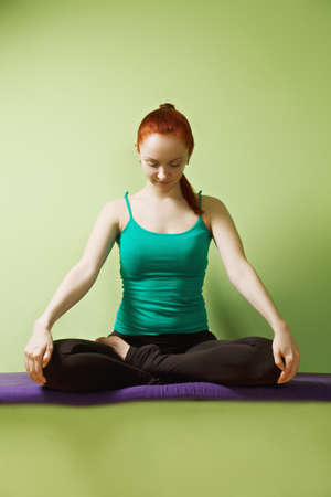 pleasant emotions: Relaxed redhead caucasian woman meditatind in lotus yoga pose at the green wall Stock Photo