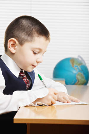 sideview: Caucasian boy wearing formal school wear writing at the desk in classroom sideview