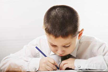 Caucasian kid wearing formal school wear writing at the desk in classroom