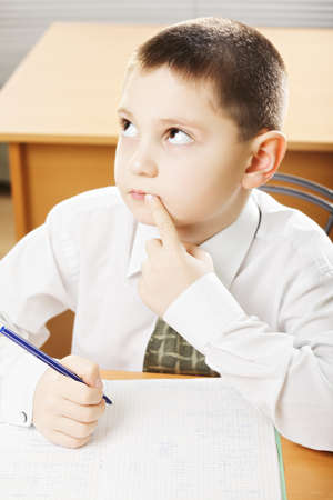 formal wear: Caucasian schoolboy in formal wear looking up while solving task