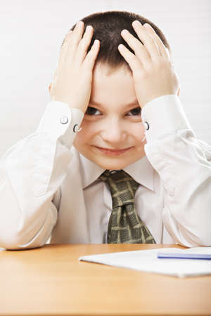 formal wear: Positive caucasian schoolboy in formal wear at the desk Stock Photo