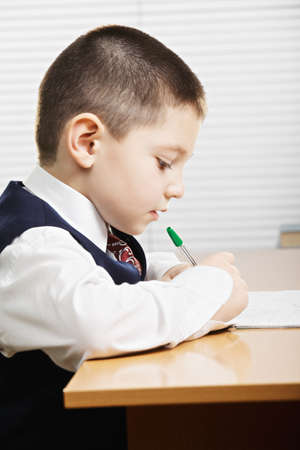 profile view: Caucasian boy wearing formal school wear writing at the desk in classroom profile view Stock Photo