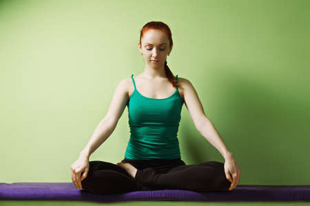 pleasant emotions: Relaxed redhead caucasian woman meditatind in lotus yoga position at the green wall