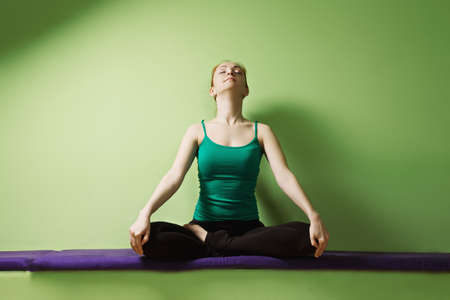 breathing: Redhead caucasian woman breathing while sitting in lotus yoga pose at the green wall