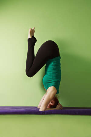 vertical wellness: Yoga woman exercising stand on head legs bent at the knees Stock Photo