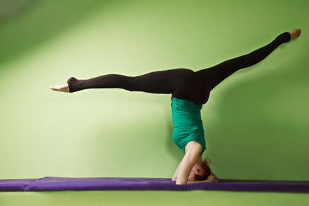headstand: Yoga woman exercising headstand with legs split on a bench at the green wall