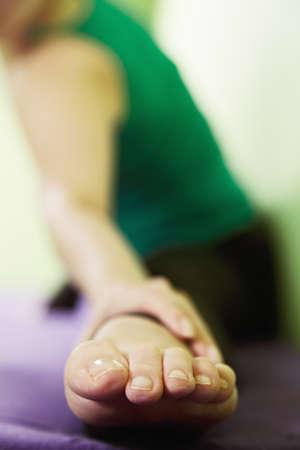 hatha: Foot of woman exercising hatha yoga at the green wall selective focus Stock Photo